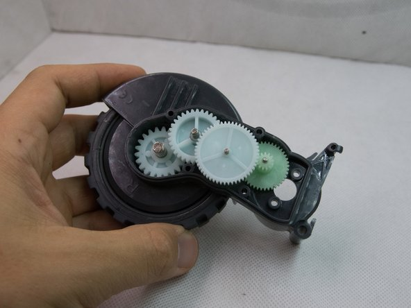 With the motor out of the equation, try to move the wheel. If it's still stuck, than the problem is most likely the fibre buildup inside the wheel housing - as expected