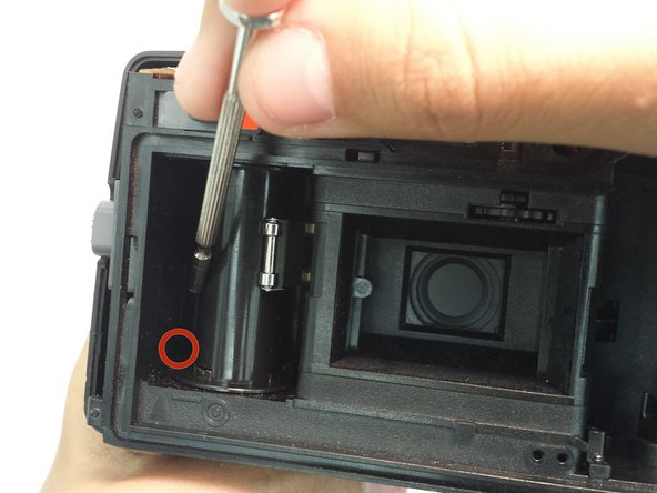 Using a thin shaft screwdriver, unscrew the two indicated screws within the film compartment.