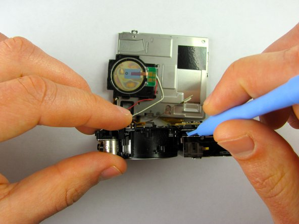 Once the bottom portion of the camera is removed, stand the camera  upright, bottom portion facing up, then detach the inner orange strip from the motherboard to the lens by inserting the plastic opening tool under the tab and lifting up.