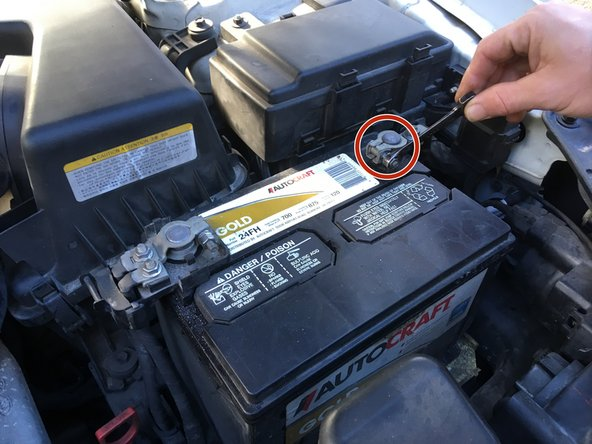 Locate the car battery and use the ratchet to loosen the negative (-) cable.