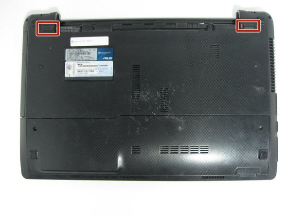 Image 1/3: Push the two locking mechanisms at the top of the laptop outward and pull the battery away from the laptop.