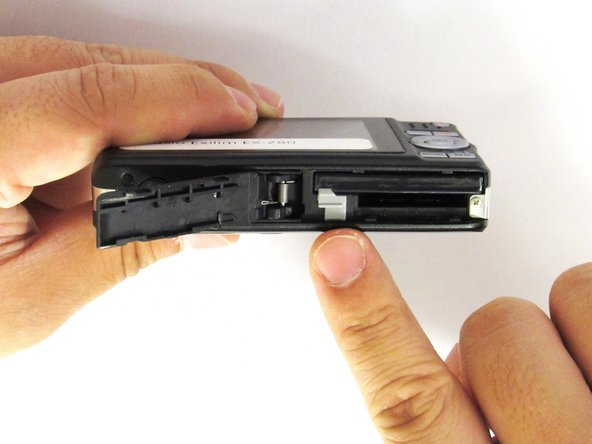 With your index finger, gently pull back gray release lever for the battery to pop out.
