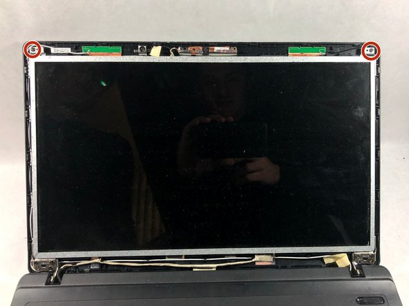 Remove the two 9mm screws from the top corners of the display with a Phillips #000 screwdriver.