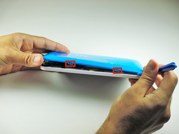Slide the plastic opening tool around the edge of the device. Gently pry apart the tabs that hold the front cover and the back cover together.