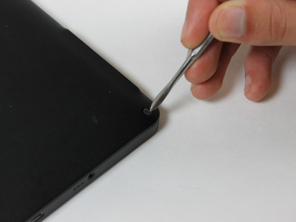 Remove the screw covers from each corner of the back side of the device.