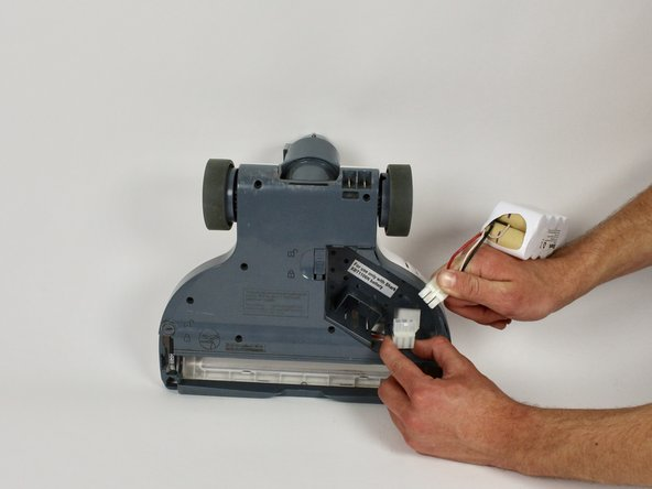 Disconnect the battery from the vacuum by pinching the white latch and pulling the two pieces apart.