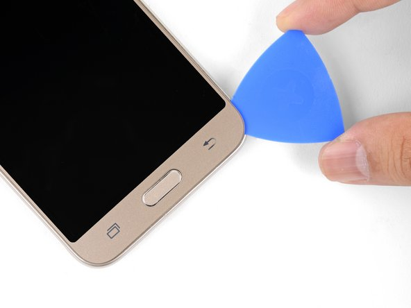 Continue cutting the adhesive with the opening pick, rounding the bottom right corner and slicing through the bottom bezel area.