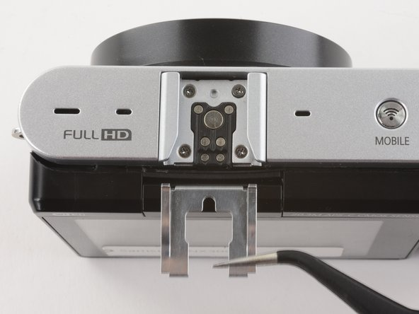 Use tweezers to pull the metal shield straight out of the external flash mount.