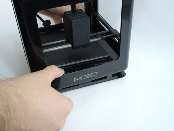 Place pressure on the central print bed and simultaneously pull up on the outer perimeter of the 3D printer. The cube shaped enclosure will lift up.