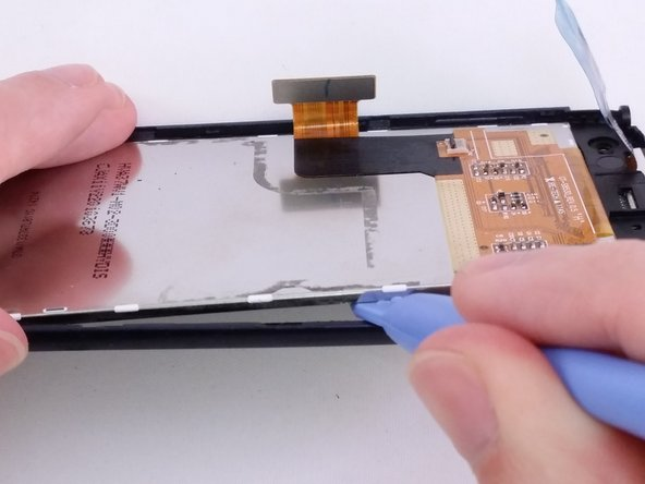 Use plastic opening tool to pry and lift the LCD from the glass screen.