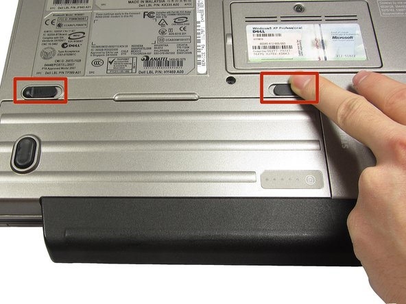 Using two index fingers, slide the battery latches outward.