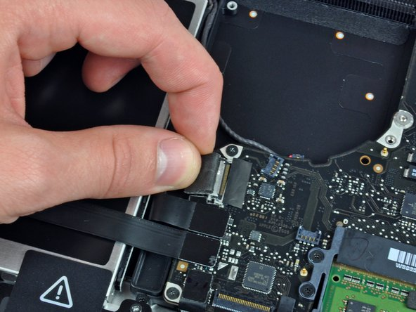 In this step you will disconnect the camera cable. Most machines will have a small self adhesive plastic retainer stuck to the logic board to keep the connector in place. Before disconnecting the cable, be sure this retainer is moved out of the way.