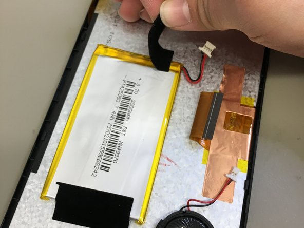 Image 1/2: with a plastic piece, lift battery from adhesive securing it in place.