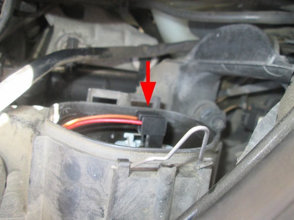 Image 1/1: This is done by unplugging the low beam socket (it's stuck in with friction, and wiggles right out), unhooking the fastener holding the bulb in place, replacing the bulb, and sticking everything back together afterwards. (See Step 8 for details.)