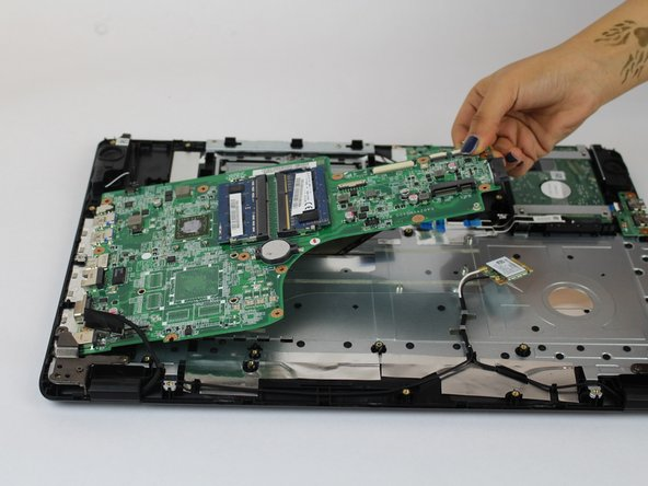 Lift the motherboard up from the narrow side and jiggle slightly so that way it doesn't get caught on the ports of the laptop case.