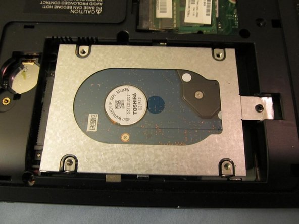 Image 1/1: Next, remove the single screw holding the hard drive in place (it's located on the right).