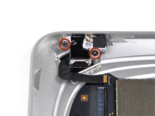 Remove the two 2.8 mm T5 Torx screws securing the headphone jack to the rear case.