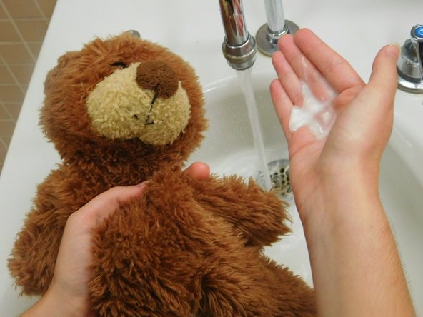 Using cold water and mild soap, hand wash the fabric of the bear.