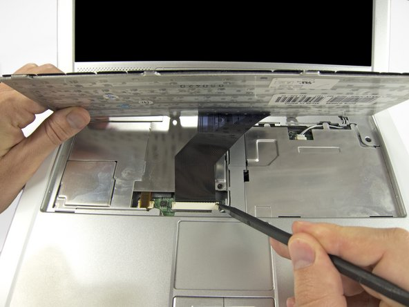 Tilt the bottom of the keyboard up at an angle, and use the pointed end of a spudger to disconnect the ribbon cable by pushing open the clips on either side.