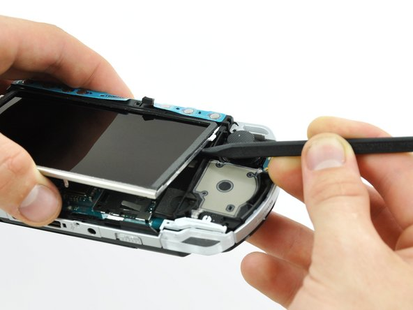 Insert a spudger under the LCD, beside the black plastic tab.