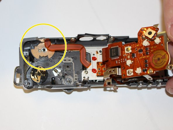 With the top panel and metal plate removed, locate the zoom control on the underside of the panel (located on the forward left side if the panel is oriented similarly to the first image.) It will be located directly under the metal plate and circuit ribbon that was removed in the previous step.