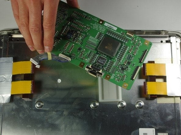 Image 2/2: Remove the circuit board from the right side of the unit by gently lifting it out.