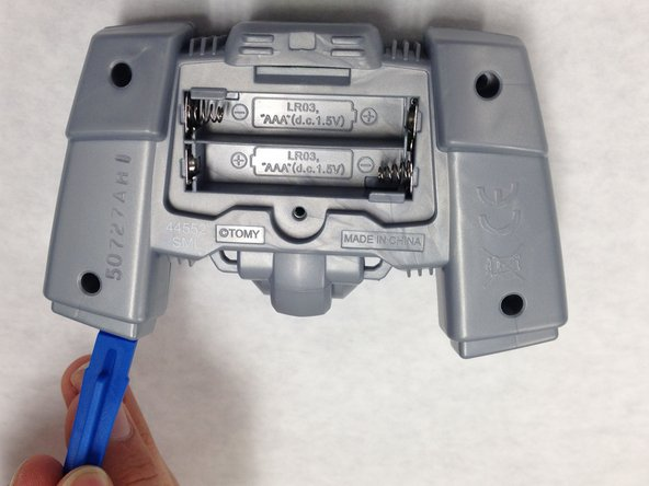 Use the plastic opening tool to disconnect the front and back parts of the panel.