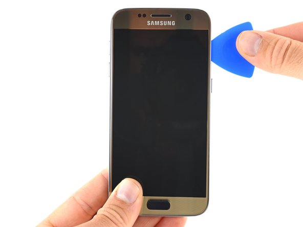 Slide the opening pick down the side of the phone, separating the adhesive.