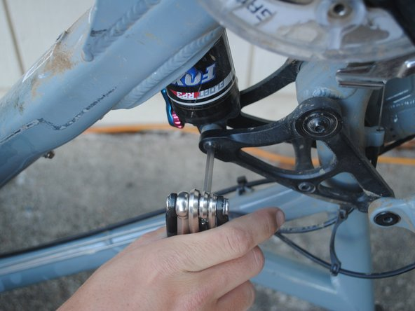 Remove the 40mm screw that connects the shock to the link arm of the suspension.