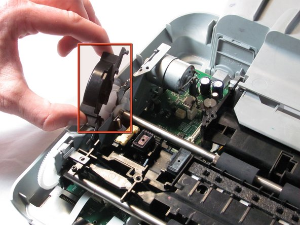 Remove the plastic gear cover by pulling it away from the printer body and lifting it up.