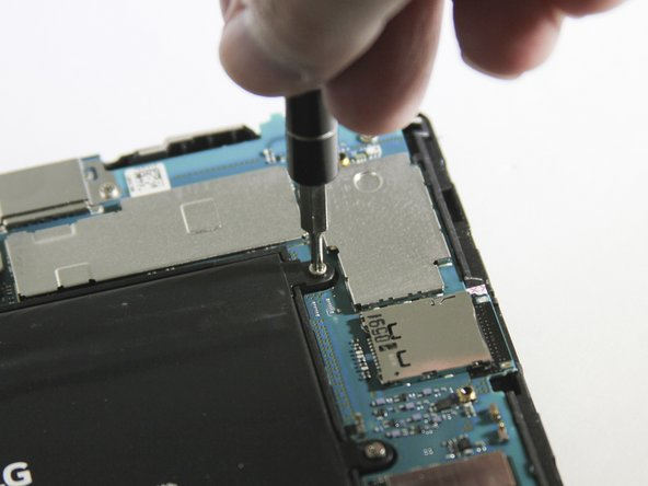 With the Phillips #000 screwdriver, unscrew the two 4.0 mm screws that hold down the battery ribbon connector.