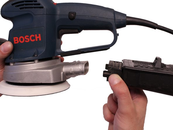 Press the pinch point tabs located on each side of the dust canister and slide the dust canister away from the sander.