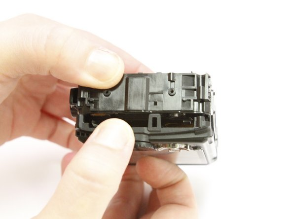 Use your fingers to unclasp the casing clips on either side of the camera and pull down the monitor casing.