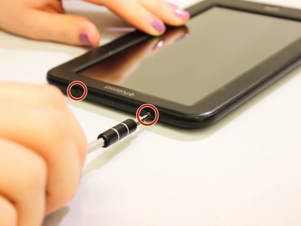 Remove the two 7 mm screws on the top of the device using a J00 Phillips screwdriver and by turning the screws counterclockwise.