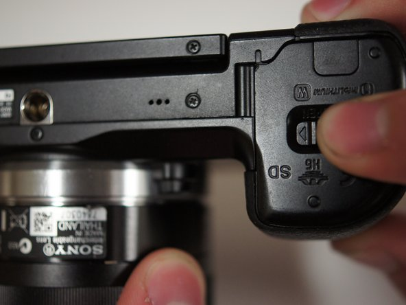 Image 1/1: Slide the switch on the bottom of the camera grip towards the lens to open the battery door.