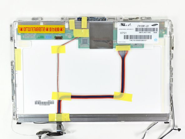 Image 1/1: Peel up all the yellow tape securing the display data and iSight cables to the back of the LCD panel.