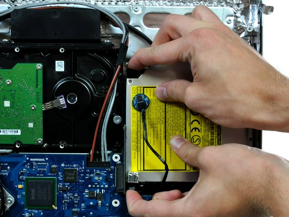 Squeeze the two optical drive bracket ears together while pulling the drive toward yourself.
