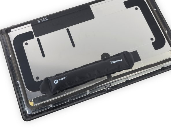 Use an iOpener near the top edge of the display assembly to heat and soften the adhesive on the piece of tape holding the thermal sensor in place.