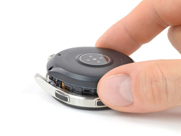 Lay down the watch and lift the back cover to access the sensor connector on the motherboard.
