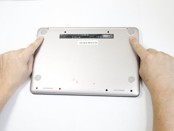 Use a metal spudger to pry off the two feet closest to the hinge of the laptop.