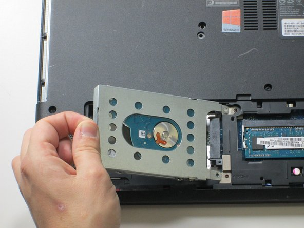 To remove the hard drive, pull up and to the left using the plastic tab as shown on the left side of the hard drive.