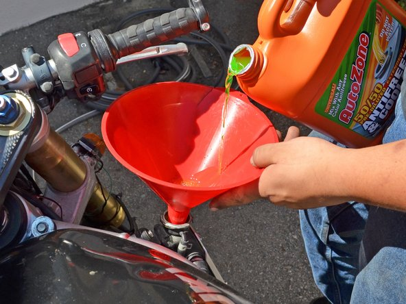 Pour approximately 1.7 quarts of coolant into the radiator or fill until you can see coolant near the filler neck. Use one hand to stabilize the funnel to prevent spills.