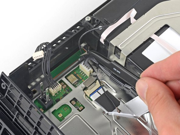 Use a pair of tweezers or your fingers to thread the antenna cable out from underneath the optical drive cable.