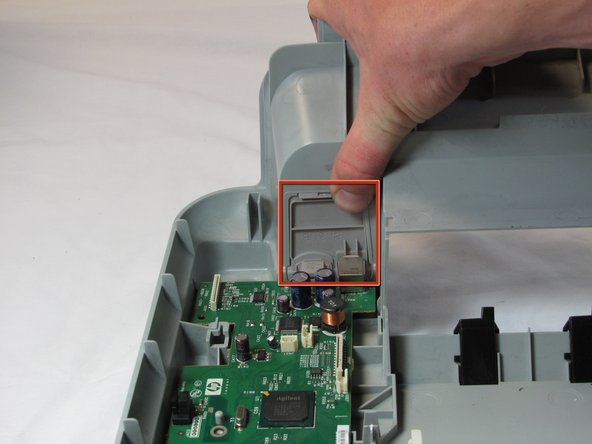 Push down on the tab that is on the power and USB back panel and then away from the printer to remove the power and USB back panel.
