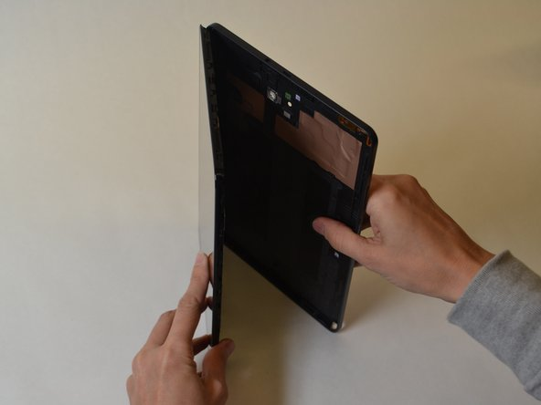 Insert a plastic opening tool between the screen and rear casing.