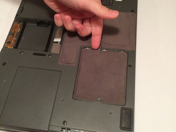 Slide the cover towards the screw, and then lift up the cover.