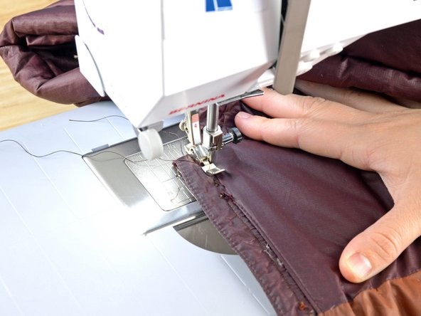 Align the jacket in the sewing machine, with the zipper webbing facing up.