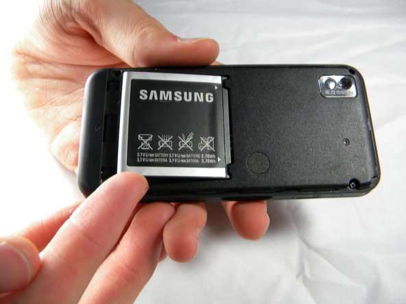 Holding the phone firmly, use the notches to grip and lift up the battery.