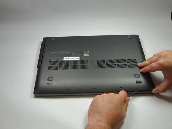 Use the spudger to separate the bottom panel from the laptop case.