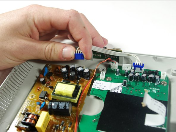 Image 2/3: Pull the white cable with the blue adapters off of the circuit boards.